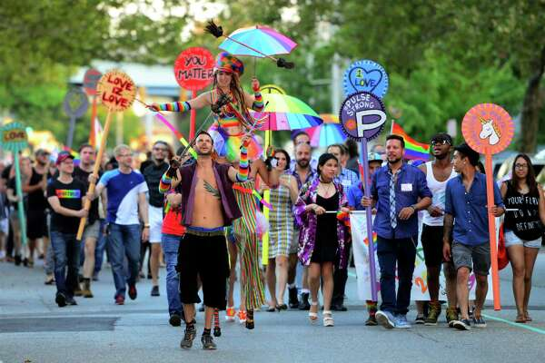 Participants walk in the 6th Annual SAMESEX 2016 Bridgeport Pride March as part of the City Lights Galery exhibit and reception in downtown Bridgeport, Conn. on Thursday July 21, 2016. The gallery event coincides with the first of the Downtown Thursdays Concert Series, which featured Latin dance groups Vinny and Ray Afro-Cuban Latin Jazz and Orquesta Afinke.
