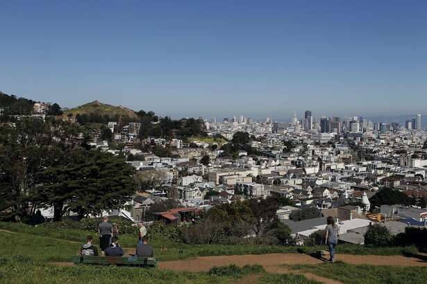 People enjoy the weather and views from Kite Hill Open Space in San Francisco, Calif., Saturday February 21, 2015.