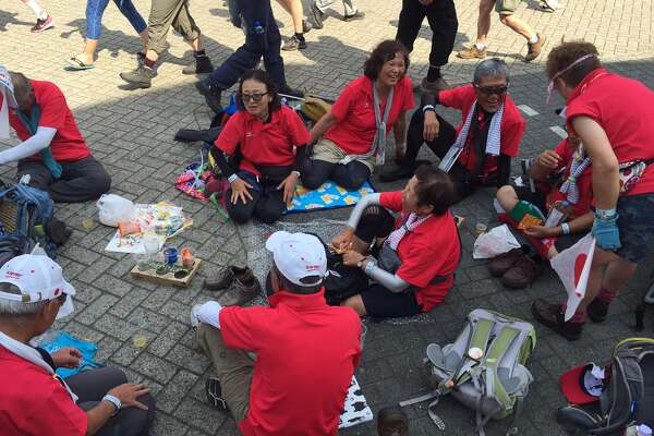 "A group of walkers from Japan rests after finishing ""The Walk of the World"" Thursday in Nijmegen (Paul Grondahl / Times Union)"