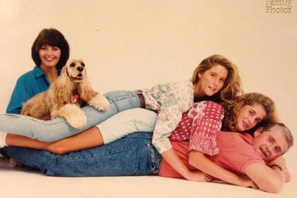 "Stacked: ""My Mom booked this photo shoot. I was 12 and my sister was 15. We have no idea why the photographer thought laying in a pile on my Dad would make a good photo. And how did Mom get out of it? She must have known then how ridiculous it would look. Moms know everything."""