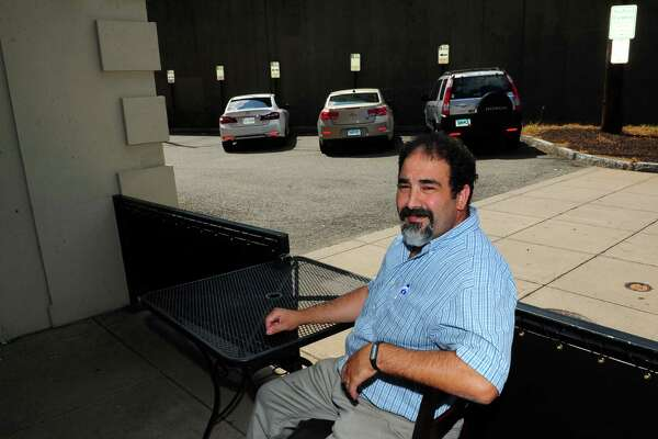 Nick Jhilal poses at his restaurant Maxwell's American Grille where nighttime parking has become a problem in downtown Stratford, Conn. on Tuesday July 20, 2016. Jhilal says there is a two hour time limit on all the spots and there aren't enough to handle all the businesses open in the area.
