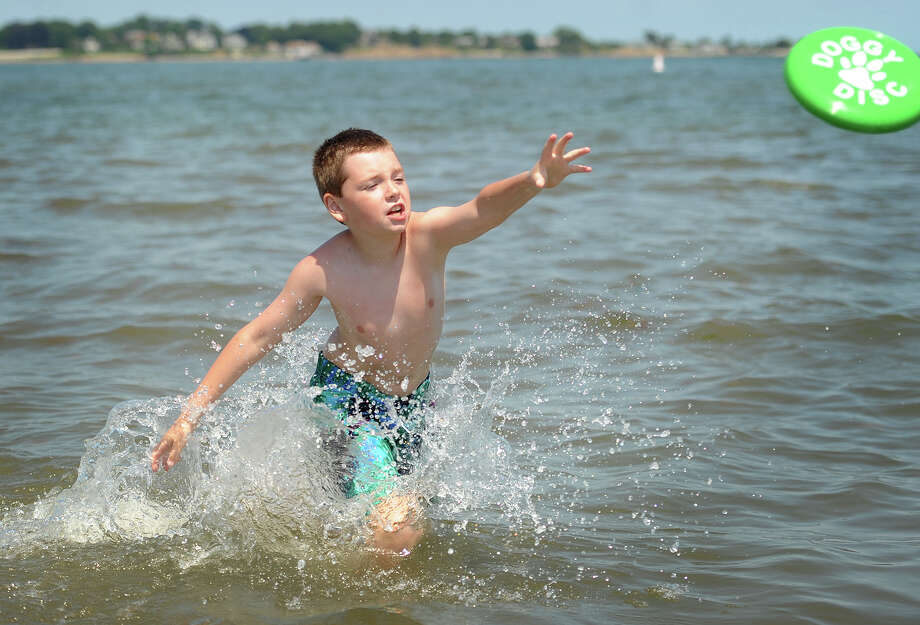 Stephen Paul, 9, of Shelton, enjoys a game of frisbee in the water during a visit to Silver Sands State Park in Milford, Conn. on Monday, June 20, 2016. Monday was the first official day of summer with the summer solstice occuring at 6:34 pm. The weather forcast this week is for a combination of sun and clouds with daytime temperatures hovering near 80 degrees. Photo: Brian A. Pounds / Hearst Connecticut Media / Connecticut Post