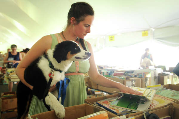 Kalia Lydgate, of Colrain, Mass. browses for books with her dog Bellatrix at he Pequot Library's 56th annual summer book sale, in Fairfield, Conn. July 22, 2016.