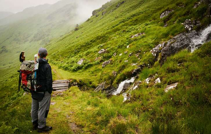 Hiking the misty trail through the Scottish Highlands, dotted with waterfalls.