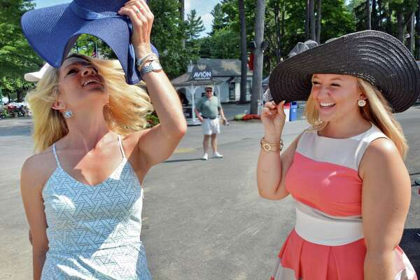 Jill Deitrick, left, of Duryea, Penn., and Stephanie Ward of Kirkwood, NY, learn to handle floppy hats in a breeze on opening day at Saratoga Race Course Friday July 22, 2016 in Saratoga Springs, NY.  (John Carl D'Annibale / Times Union)