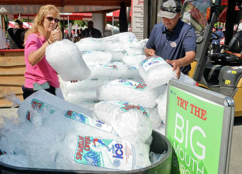 Lucinda Ritchie, left, and Pablo Zuniga of Centerplate stock up on ice as temps are expected to hit 90 on opening day at Saratoga Race Course Friday July 22, 2016 in Saratoga Springs, NY. (John Carl D'Annibale / Times Union)