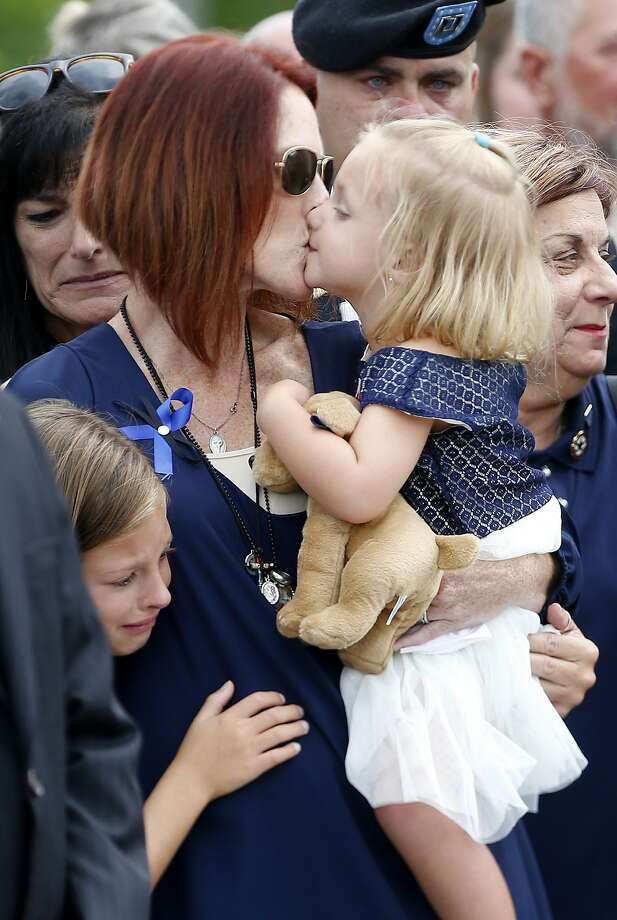 Dechia Gerald, wife of slain Baton Rouge police officer Matthew Gerald, kisses her daughter Fynleigh, as her other daughter Dawclyn, left, cries, while Gerald's casket is loaded into a hearse, after funeral services at the Healing Place Church in Baton Rouge, La., Friday, July 22, 2016. Multiple police officers were killed and wounded Sunday morning in a shooting near a gas station in Baton Rouge, less than two weeks after a black man was shot and killed by police here, sparking nightly protests across the city. (AP Photo/Gerald Herbert) Photo: Gerald Herbert, Associated Press