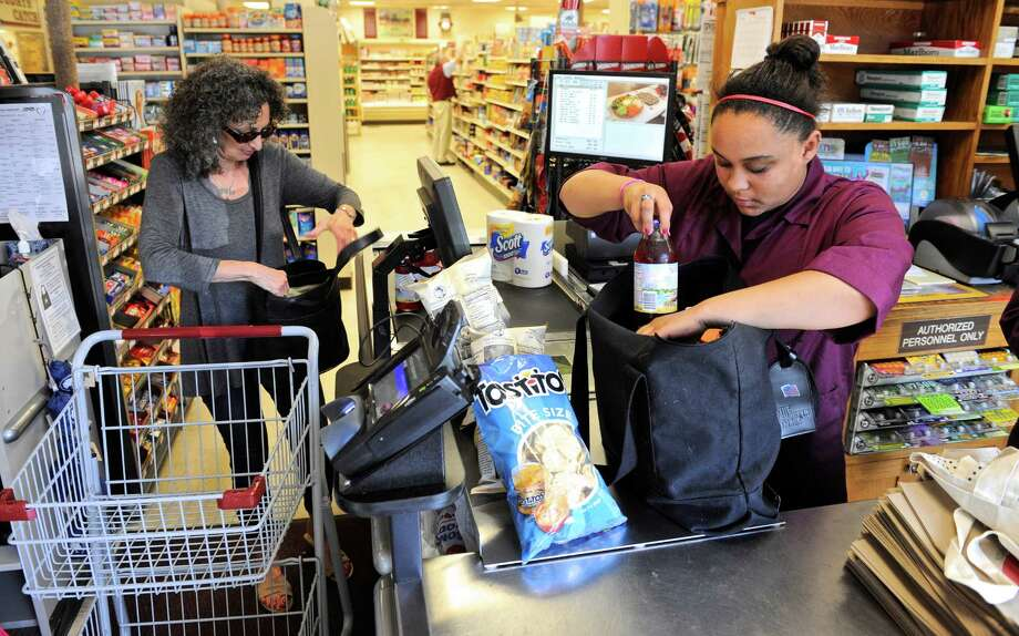 "Sadie Feleming, 18, of Washington, packs groceries for Florence Minor, of Washington, in a reusable tote bag at the Washington Food Market. The Washington Environmental Council's ""The Good Bag"" program is trying to eliminate the single use checkout counter bag buy encouraging the use of reusable tote bags. Wednesday, July 20, 2016, in Washington, Conn. Photo: H John Voorhees III / Hearst Connecticut Media / The News-Times"