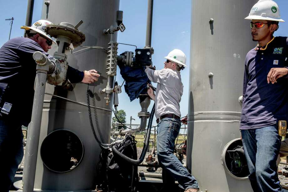 Southwestern Energy workers check on a suspected pipe leak at a well pad site in Damascus, Ark., June 28, 2016. The reputation of natural gas as a 'clean energy' in the fight against climate change rests in part on the abilities of workers tracking down and eliminating methane leaks in the nation's pipeline infrastructure. (Andrea Morales/The New York Times) Photo: ANDREA MORALES, NYT / NYTNS