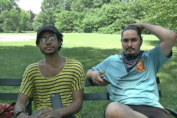 """In this July 13, 2016 frame grab from video, Jordan Clark, left, and Lewis Gutierrez sit in Prospect Park as they talk about their new """"Pokemon Go"""" business in the Brooklyn borough of New York. They are among the new entrepreneurs who offer their services as """"trainers"""" for the game at $20 per hour - logging onto a client's """"Pokemon Go"""" account and effectively running up their score while a client is stuck at work or sitting in class. (AP Photo/Ezra Kaplan)"""