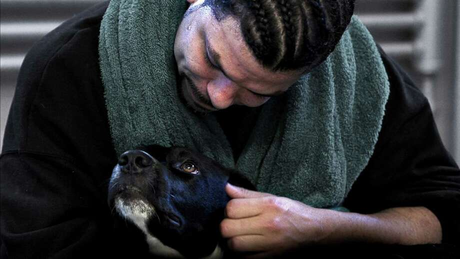 """Dogs On The Inside"" will be screened at Bethel Cinema on Wednesday, Aug. 3, as part of FilmFest52. Inmate Candido Santiago, who appears in the movie, is seen here comforting his dog, Byram. Photo: Bond /360 / Contributed Photo"