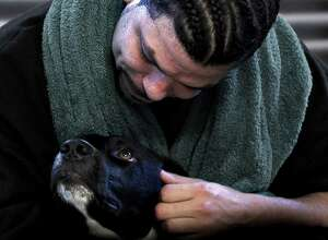 """""""Dogs On The Inside"""" will be screened at Bethel Cinema on Wednesday, Aug. 3, as part of FilmFest52. Inmate Candido Santiago, who appears in the movie, is seen here comforting his dog, Byram."""