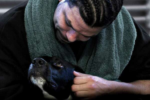 """Dogs On The Inside"" will be screened at Bethel Cinema on Wednesday, Aug. 3, as part of FilmFest52. Inmate Candido Santiago, who appears in the movie, is seen here comforting his dog, Byram."