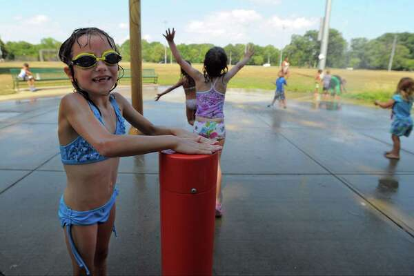 Helen Deren, 7, of Stamford , cools off while playing in the Splash Pad water feature at Scalzi Park in Stamford, Conn. on July 22, 2016. Temperatures reached into the high 90's for most parts of Southern Connecticut, with a cooler temperatures predicted for the weekend.