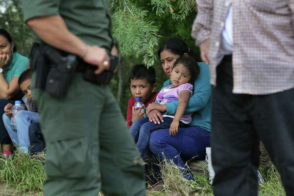 In this June photo, immigrant mothers sit with their children as Border Patrol Agent Isaac Villegas, left, talks with a man that was traveling in the group from Central America that were apprehended during a patrol on a ranch near Fronton. Temporary work cards could help stem the tide of immigrants crossing the border illegally under dangerous conditions.