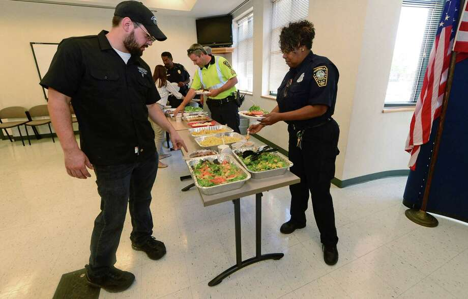 Johnny Utah's chef and kitchen manager, Cory Rizzolo, describes the spread for Norwalk police Officer Melissa Lee, as the restaurant serves up lunch for officers and staff at the Norwalk Police Department on Tuesday, July 19. Photo: Erik Trautmann / Hearst Connecticut Media / Norwalk Hour
