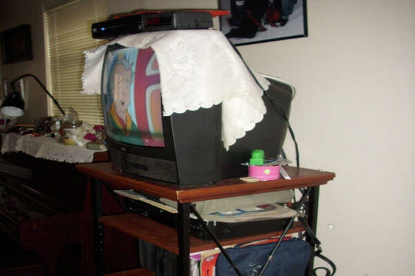 A box-style television on top shelf of a stand with a cable box on top of the television. Both are within reach of a toddler's playpen, which could pose a tipping hazard should a child use the shelving to stand or climb. A 2012 review by the Department of Health and Human Services determined that of 20 family day care home providers inspected, most did not always comply with state health and safety licensing requirements.