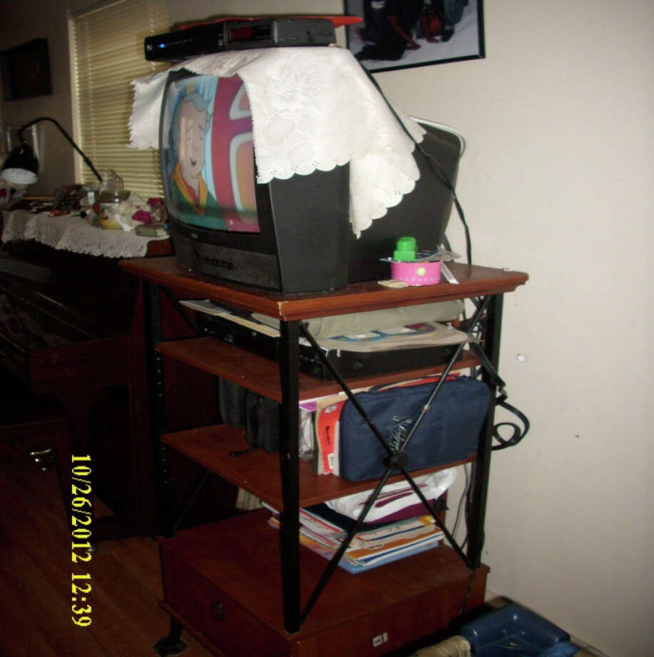 A box-style television on top shelf of a stand with a cable box on top of the television. Both are within reach of a toddler's playpen, which could pose a tipping hazard should a child use the shelving to stand or climb. A 2012 review by the Department of Health and Human Services determined that of 20 family day care home providers inspected, most did not always comply with state health and safety licensing requirements. Photo: Contributed Photo / Contributed Photo / Connecticut Post