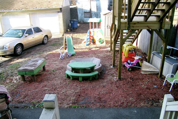 A children's outdoor play area without a fence or protective barrier to prevent children from entering the driveway where cars are parked. Also shown is a set of stairs without protective gates. A 2012 review by the Department of Health and Human Services determined that of 20 family day care home providers inspected, most did not always comply with state health and safety licensing requirements.