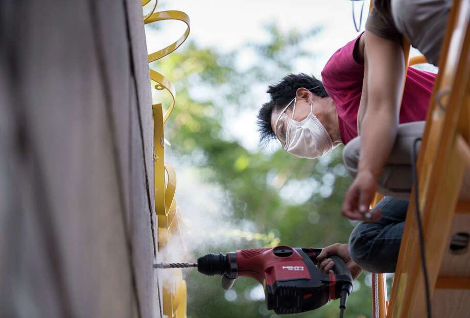 "New York artist Suikang Zhao works on his sculpture, ""Gatevine,"" a community art installation on West Avenue in Norwalk. Zhao was chosen from 144 entries to create the work, which stretches from the Route 7 connector overpass to the I-95 overpass along the retaining wall of West Avenue. Photo: Autumn Driscoll / For Hearst Connecticut Media / Autumn Driscoll  Connecticut Post Freelance"