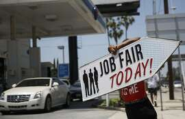 """An Aarrow Sign Spinners representative spins a """"Job Fair Today"""" sign during a Choice Career Fair in Los Angeles, California, U.S., on Wednesday, June 22, 2016. The U.S. Department of Labor is scheduled to release initial jobless claims figures on June 23. Photographer: Patrick T. Fallon/Bloomberg"""