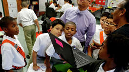 """Principal Derrick Brown beams as he checks in on a project based learning activity with Kaiden Carroll, from left, Isak Cardenas, Bryson Adams, Francisco Vigil, Christopher Duquette and Rico Carpenter during their fourth grade math class with teacher Leola Lawerence, right, on Oct. 13, 2015. """"We completely did away with the structure and our focus is on engaging the learner,"""" says Principal Derrick Brown."""