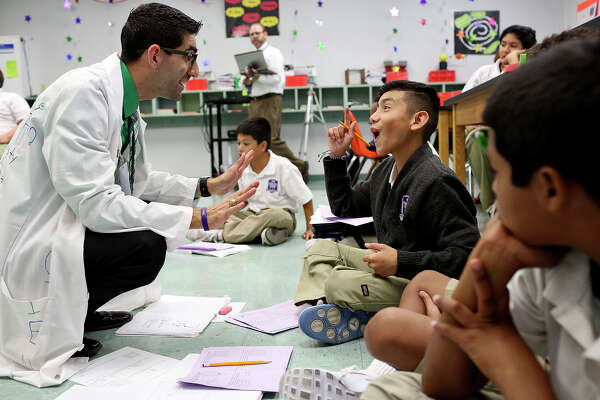 """Science teacher JB Maldonado, left, talks with 6th grader Michael Pike during their class at YMLA on Sept. 22, 2015. Maldonado was attracted to the school's principles of character, discipline and leadership. """"Those are the goals IÕve always set for myself and I want to be able to instill that into the children that hopefully I do touch their lives in a positive way and I do want to instill that into them. This is a perfect environment to do this. A school thatÕs going to base themselves on that,"""" says Maldonado."""