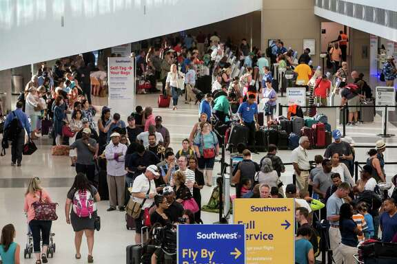 Southwest Airlines passengers stand in line at the ticketing/checking counter at Hobby Airport on Thursday, July 21, 2016, in Houston. A computer problem in the Southwest Airlines system caused flights across the country to be held up or cancelled as the airline worked to fix technology problems. ( Brett Coomer / Houston Chronicle )