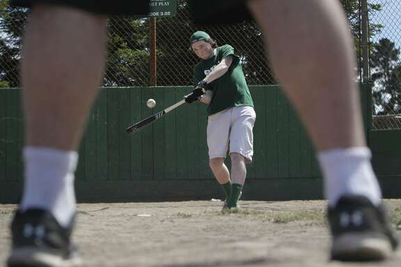"Sean White (center), 16, hits a baseball during batting practice with friend Pierce Parnell (feet in foreground) , 15, at Junipero Serra Playground on Tuesday, July 19, 2016 in San Francisco, California.  White had wrist bands with the motto: Team Sean  ""We Got This!""  made before his last open heart surgery which he sold to raise funds for donation."