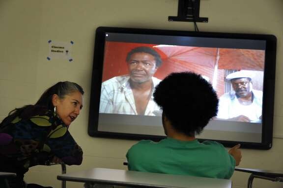 "Alysse Castro (l to r), director of Alternative High Schools, talks with a student as he watches ""Do the Right Thing"" during cinema studies at the Juvenile Justice Center's Woodside Learning Center on Wednesday, July 20, 2016 in San Francisco, California."