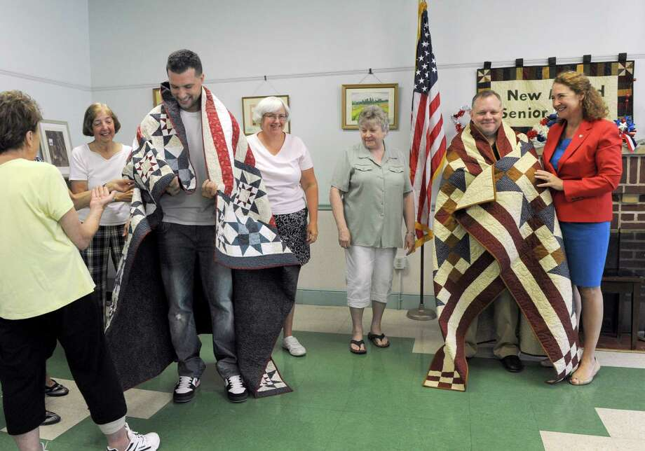 Veterans Robert Madorran, left, and Mike Zacchea, right, with quilters from the New Milford Senior Center, and Congresswoman Elizabeth Esty, right, are playfully wrapped in their quilts. The veterans were presented with Quilts of Valor in a ceremony presided over by Congresswoman Elizabeth Esty and Mayor David Gronbach at the New Milford Senior Center Friday morning, July 22, 2016. Photo: Carol Kaliff / Hearst Connecticut Media / The News-Times