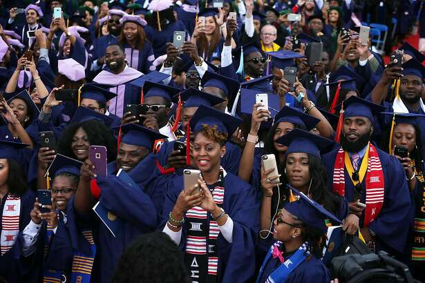 WASHINGTON, DC - MAY 07:  Members of the class of 2016 take pictures with their smartphones as U.S. President Barack Obama addresses the 2016 commencement ceremony at Howard University May 7, 2016 in Washington, DC. President Obama is the sixth sitting U.S. president to deliver the commencement speech at Howard University.  (Photo by Alex Wong/Getty Images)
