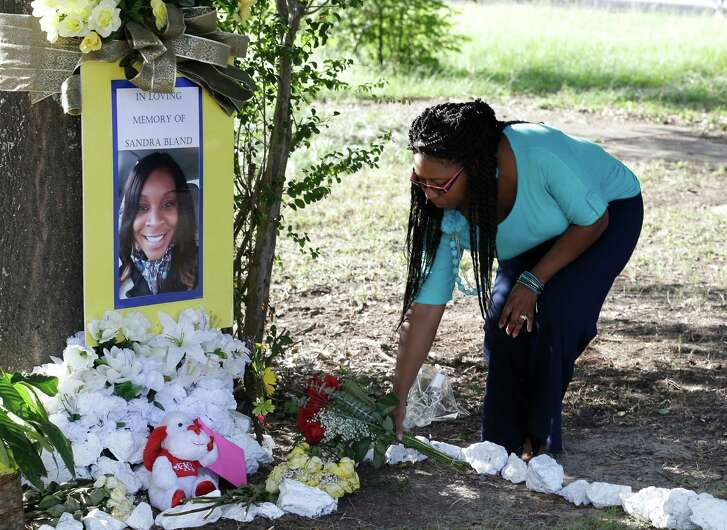 FILE - In this July 21, 2015 photo, Jeanette Williams places a bouquet of roses at a memorial for Sandra Bland near Prairie View A&M University, in Prairie View, Texas. Vigils and ceremonies are planned Wednesday, July 13, 2016, to mark the one-year anniversary of the death of Bland, a black woman who died in a Texas jail cell after a traffic stop. Her death was ruled a suicide. (AP Photo/Pat Sullivan, File)