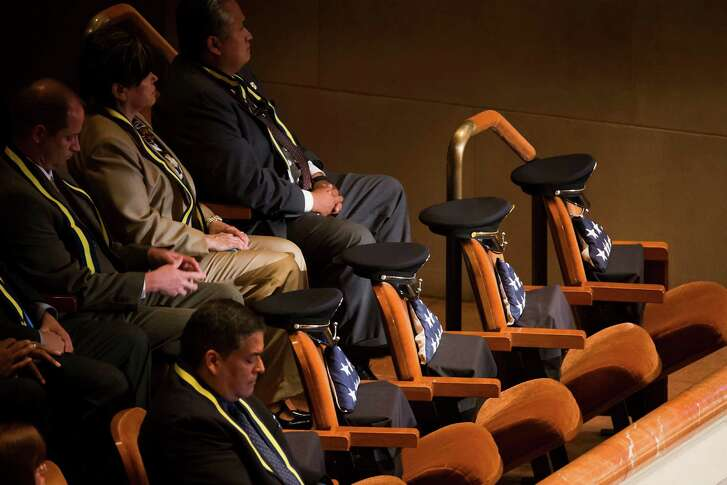 Empty seats for fallen law enforcement officers were on display at an interfaith memorial service in Dallas on July 12 for five officers killed in an ambush at a Black Lives Matter rally. (Smiley N. Pool/The Dallas Morning News)