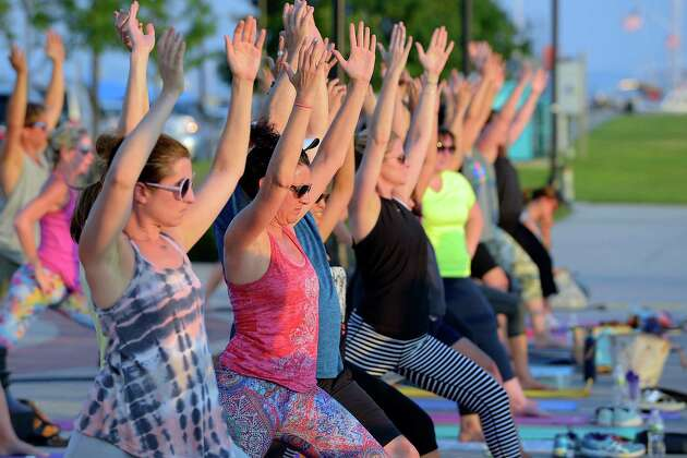 Yoga enthusiasts participate in a yoga class during the 4th annual Yoga Jam on the boardwalk at Harbor Point in Stamford, Conn. on July 22, 2016. Over three hundred participants enjoyed an evening of celebration with shopping, food, music, and yoga taught by Megan Kuczynski of Exhale and Aimee Elsner of CT Power Yoga. The pair teamed up with lululemon athletica of Greenwich, to raise funds for the Africa Yoga Project, which educates, empowers, elevates and employs youth from Africa using the transformational practice of yoga.