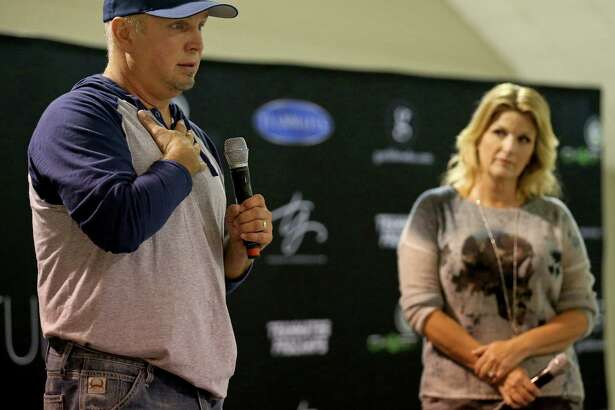 Garth Brooks answer questions from the media as his wife Trisha Yearwood looks on during a press conference held Friday July 22, 2016 in the Rodeo Auction Room at AT&T Center.