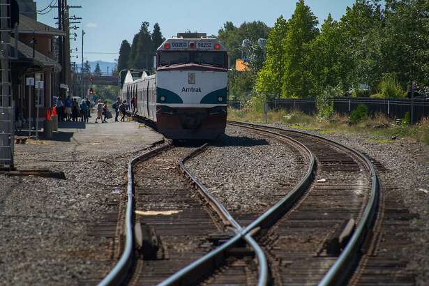 This July 13, 2016, photo shows passengers getting on an Amtrak Cascades train in Eugene, Ore. The Register-Guard reports that the Oregon Department of Transportation is planning to keep the passenger rail line in its current location on the Union Pacific Railroad tracks. The railroad owners focus on moving freight, causing delays for passengers. (Brian Davies/The Register-Guard via AP)
