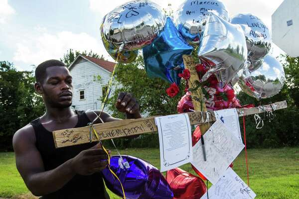 Chris Lavigne, a friend of shooting victim Damarcus Tucker, ties a balloon onto a makeshift memorial at the corner of Napoleon and Rosalie on Thursday.