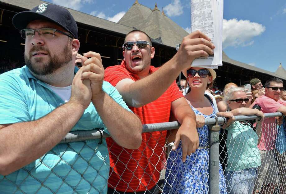 Race fans, from left, Dominick Baker, of Schenectady, Joe Paone of Schenectady and Marissa Martinekof Colonie cheer on their picks in the first race on opening day at Saratoga Race Course Friday July 22, 2016 in Saratoga Springs, NY.  (John Carl D'Annibale / Times Union) Photo: John Carl D'Annibale / 20037398A