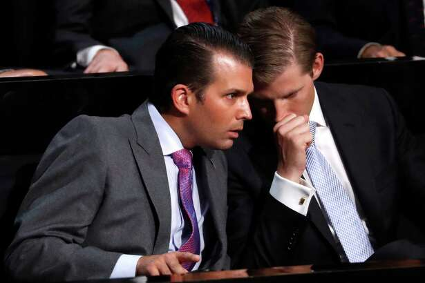 Eric Trump, right, son of Republican Presidential nominee Donald J. Trump, talks to Donald Trump, Jr., as their father speaks during the final day of the Republican National Convention in Cleveland, Thursday, July 21, 2016. (AP Photo/Paul Sancya) ORG XMIT: RNC360