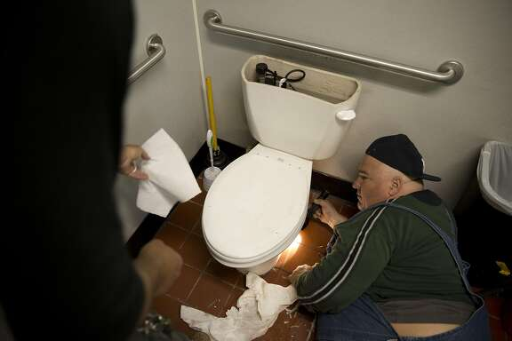 Keith Barbarino helps Tony Fazule fix a leaky toilet at Happy Hound Play & Daycare on Thursday, July 21, 2016 in Oakland, Calif.  Barbarino, 25, recently moved to Oakland to apprentice with Fazule.
