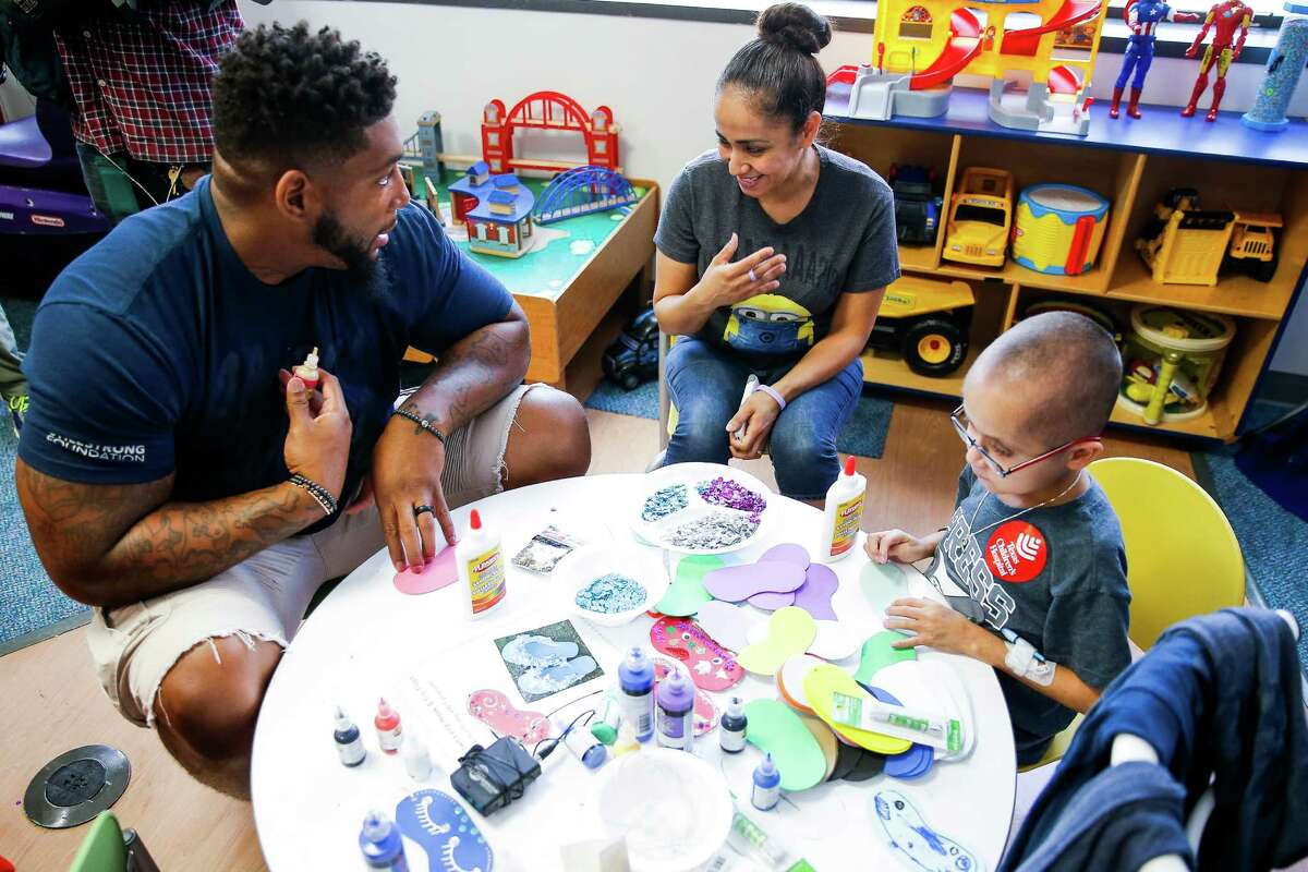 Houston Texans defensive end Devon Still talks with Rosa Bermudez, center, while making crafts with her son, Mark Lerma, 15, who has stomach cancer, Friday, July 22, 2016 at the Texas Children's Hospital . Still's daughter, Leah Still, was diagnosed with neuroblastoma in 2014 and just beat the rare form of cancer earlier this year. Still and Leah created the Still Strong Foundation to provide financial support to families with children battling cancer.