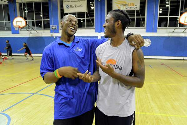 Barry Woods and Glenn Jones chat it up during a break in action of a basketball game on Thursday at the Yerwood Center in Stamford. The center is hosting a new basketball league, under the direction of Woods, nightly from 8 to around midnight. It's in response to a lack of resources for young adults and teens in the neighborhood and the recent gun violence.