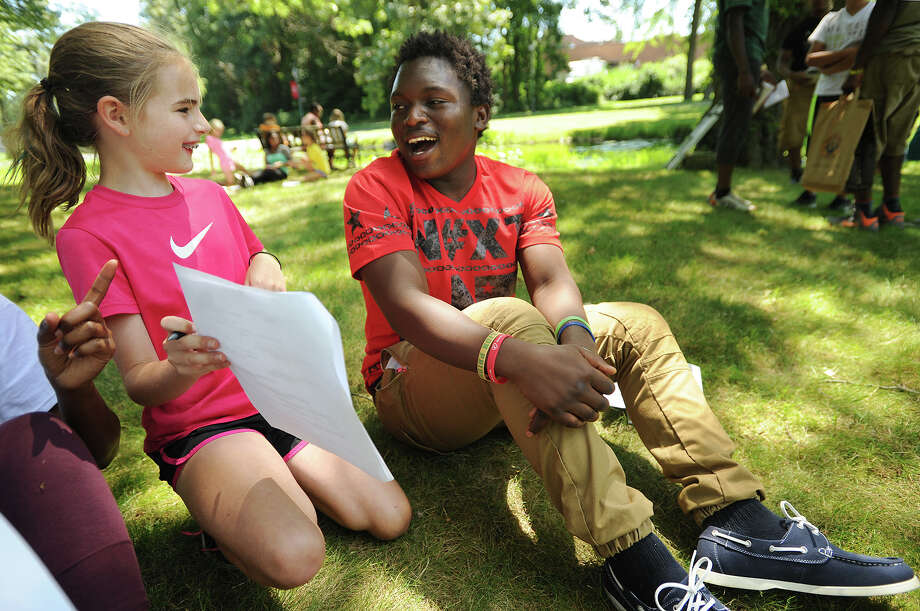 Megan Sherriff, 10, of Fairfield, works with Tanzanian refugee Juma Bonneface, of Bridgeport, a Bassick High School junior, for a two-voice poetry writing exercise at Fairfield University on Wednesday. Photo: Brian A. Pounds / Hearst Connecticut Media / Connecticut Post