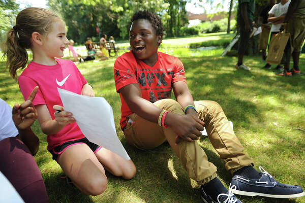 Megan Sherriff, 10, of Fairfield, works with Tanzanian refugee Juma Bonneface, of Bridgeport, a Bassick High School junior, for a two-voice poetry writing exercise at Fairfield University on Wednesday.