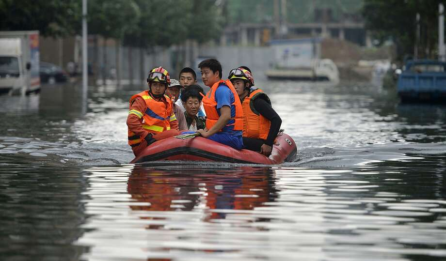 In this Thursday, July 21, 2016, photo, rescuers use a raft to transport people along a flooded street in Shenyang in northeastern China's Liaoning Province. Dozens of people have been killed and dozens more are missing across China after a round of torrential rains swept through the country earlier this week, flooding streams, triggering landslides and destroying houses. (Chinatopix Via AP) Photo: Associated Press