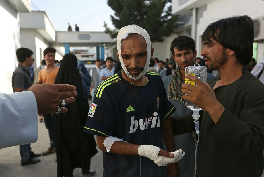 Afghans help a man who was injured in the suicide blast that struck a protest march in Kabul. Photo: Rahmat Gul, Associated Press