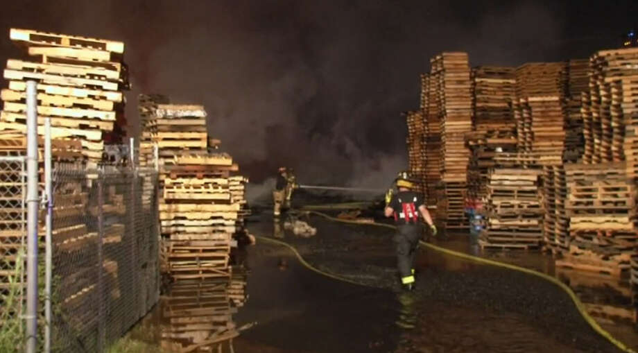 Almost 10 hours and at least 75,000 gallons of water later, a massive fire early Saturday July 23, in a northeast Harris County pallet yard is under control but still active. Photo: Metro Video