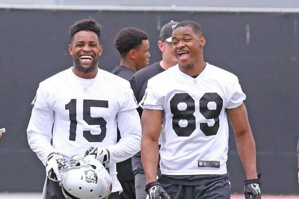 Amari Cooper (89) enjoys a laugh with teammate Michael Crabtree.