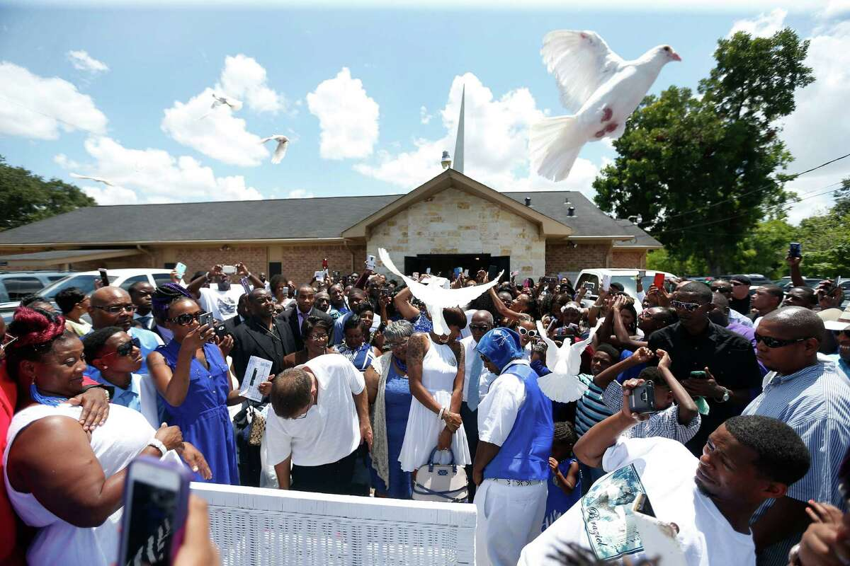 The Nikki Braziel, wife of Alva Braziel, the 38-year-old man shot by police on July 9 while waving a gun in the middle of Cullen, is surrounded by friends and family after his funeral as they released doves at New Light Baptist Church, Saturday, July 23, 2016, in Houston. Questions remain about the shooting.